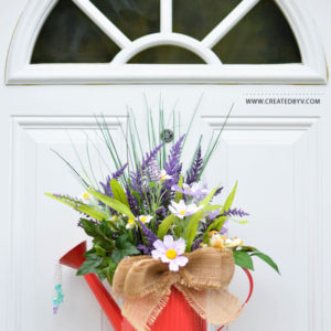 Achieve this whimsical look by turning an everyday watering can into lovely door decor in three easy steps!