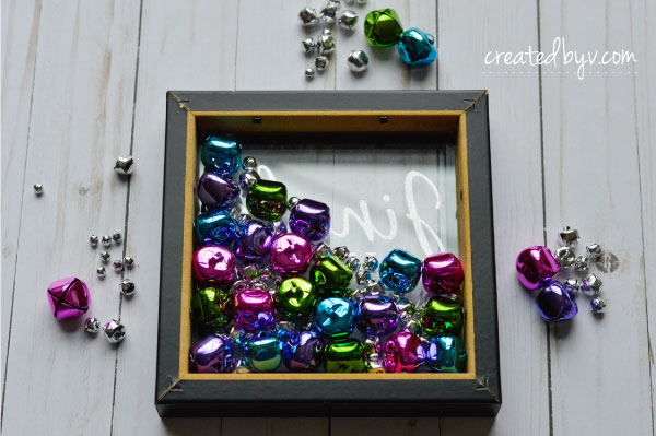 Add a touch of sparkle to your holiday decorations by turning an ordinary shadow box into a fun and festive Jingle Bells Shadow Box.
